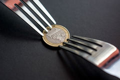 Euro crisis. Metaphoric concept of tight budget with euro coin and two forks on black background Royalty Free Stock Photography
