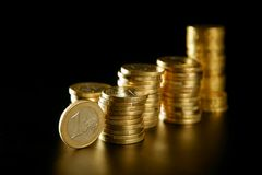 Euro currency coin columns with golden reflections Royalty Free Stock Photos