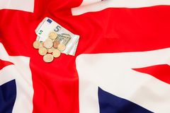 5 Euro currency and coins lie on the background of the flag of G Royalty Free Stock Photos