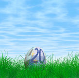 Euro currency Easter egg. Nestled on green grass with blue sky and cloudscape background stock illustration