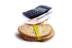 EURO currency with financial calculator. And brown slice of breads with measuring tape isolated on white background Royalty Free Stock Images