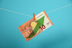 Euro currency growth illustrated over blue. European economy growth, strengthening of Euro currency, ten Euro banknote with green arrow up hanged ascending with Stock Photos