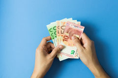 Euro currency notes. Hand with Euro currency notes over blue background Royalty Free Stock Photo
