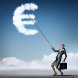 Euro currency rate. Attractive businesswoman holding on lead cloud euro currency symbol Stock Image