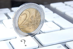 Euro Currency Uncertainty. Conceptual image of a two euro coin balanced on a keyboard with ? mark on key, defining current uncertainty in European (Euro zone) Royalty Free Stock Photos