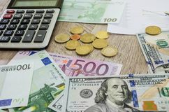 Euro, dólares, monedas, calculadora y carta de negocio en la tabla foto de archivo