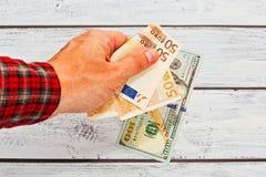 Euro d'échange de personne masculine aux dollars US image stock