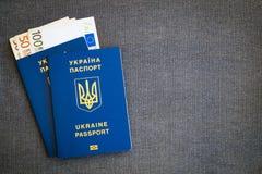 Euro d'argent et deux passeports bleus ukrainiens sur un fond en arête de poisson de tissu gris photo stock