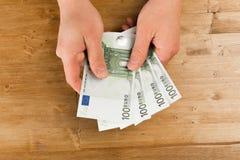 Euro da contagem do homem na tabela de madeira foto de stock