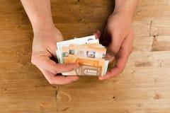 Euro de compte d'homme sur la table en bois photos stock