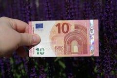 euro de la tenencia diez de la mano en un fondo púrpura oscuro imagen de archivo