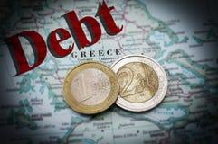 Euro debt. Euro coins on a map of Greece with Debt text (Greek financial crisis Stock Photos