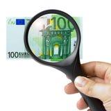 Euro della banconota 100 della lente d'ingrandimento della mano Fotografia Stock