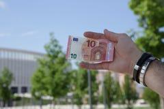 euro della tenuta dieci della mano contro il cielo blu ed il fogliame verde fotografia stock libera da diritti
