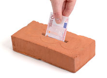 Euro deposit. Euro bank note in a piggy bank or tissue box like brick Royalty Free Stock Image