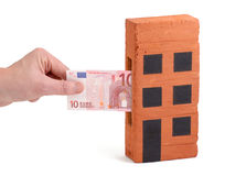 Euro deposit into a brick-house. Euro bank note being inserted to or drawn from a block of flats Stock Photography