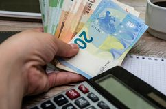 Euro in der Hand auf dem Hintergrund einer Notizbuch- und Taschenrechnernahaufnahme lizenzfreie stockbilder