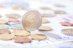 Euro deux se tenant sur des billets de banque et des pièces de monnaie Photos stock