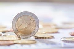 Euro deux se tenant sur des billets de banque et des pièces de monnaie Images stock