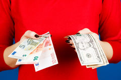 Euro and dolar in the hands of a girl Stock Photos