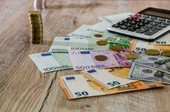 Euro, dolary, centy i kalkulator, rozprzestrzeniamy za drewnianym tle dalej zdjęcie stock