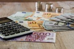 Euro, dolary, centy i kalkulator, rozprzestrzeniamy za drewnianym tle dalej obrazy royalty free