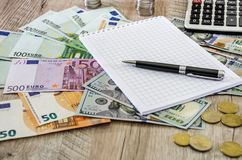 Euro, dolary, monety, notatnik, pióro i kalkulator na drewnianym tle zamkniętym w górę, obrazy royalty free