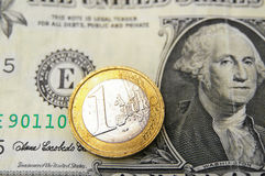 Euro and dollar. Closeup of a Euro coin on top of a US dollar bill royalty free stock photography