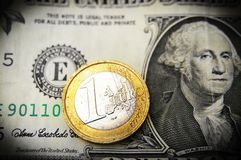 Euro and dollar. Closeup of a Euro coin on top of a US dollar bill royalty free stock photo