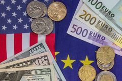Euro and dollar bills with coin on flags.  Royalty Free Stock Photography