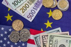 Euro and dollar bills with coin on flags.  Royalty Free Stock Images