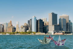 The euro and dollar boats against cityscape Stock Photo