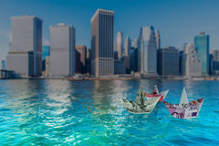 The euro and dollar boats against cityscape Royalty Free Stock Image