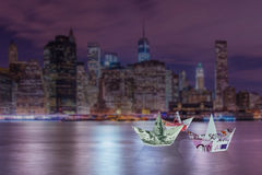 The euro and dollar boats against cityscape Royalty Free Stock Photos