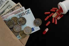 Euro and dollar currency in the envelope against scattered tablets royalty free stock photo