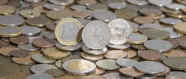 Euro, dollar et contreseing sur le fond de beaucoup de vieilles pièces de monnaie Photos stock