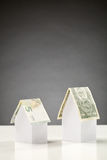 Euro and Dollar Houses. Two plain white paper houses with money as a roof - Euro and a dollar notes Stock Image
