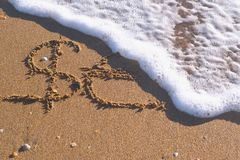 Euro and Dollar signs written in the sea sand. Waves washed away the inscription. Euro and Dollar signs written in the sea sand. Waves washed away the stock photo