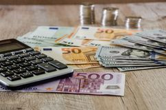 Euro, dollars, centen en calculator op een houten achtergrond uit wordt uitgespreid die royalty-vrije stock afbeeldingen