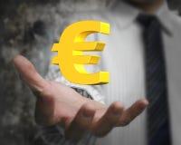Euro dorati firmano dentro la mano dell'uomo di affari Fotografia Stock