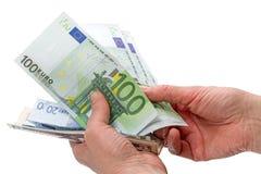 Euro e dólares nas mãos Imagem de Stock