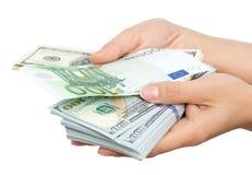 Euro e dollari a disposizione su un fondo bianco Fotografia Stock Libera da Diritti