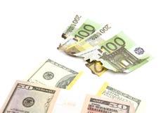 Euro e pacchetto bruciati dei dollari su bianco Fotografie Stock