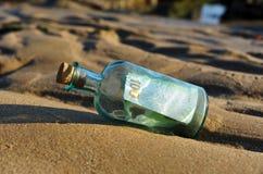 Euro 100 in einer Flasche auf dem Sand Stockbilder