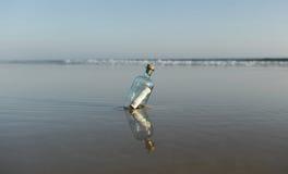 Euro 50 in einer Flasche auf dem Ufer des Ozeans Stockfotografie