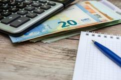 20 euro en een calculator, notitieboekje en penclose-up stock foto