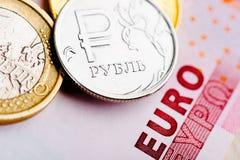Euro en roebelmuntstukken op euro bankbiljetten Stock Foto's