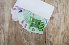 500, euro 100 en un sobre blanco en un fondo de madera Visi?n desde arriba fotos de archivo