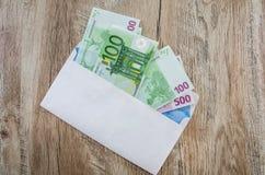 500, euro 100 en un sobre blanco en un fondo de madera Visi?n desde arriba fotografía de archivo libre de regalías