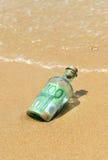 euro 100 en una botella en la playa Foto de archivo